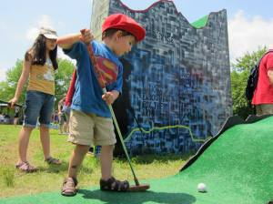 Avid mini golfer enjoying the the Figment Festival Mini Golf course. Image courtesy of Figment.