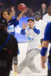 Rocsi Diaz, left, Aaron Paul and Deion Sanders compete in DIRECTV's 8th annual Celebrity Beach Bowl on Saturday, Feb. 1, 2014 in New York. (Photo by Charles Sykes/Invision/AP)